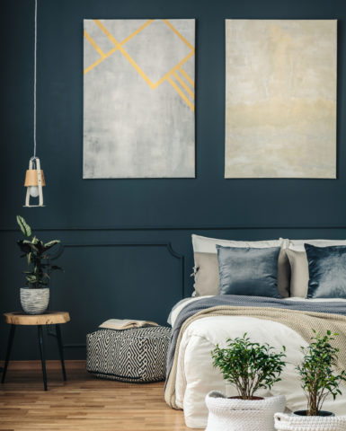 Potted plants in yarn baskets at the bottom of a cozy bed in a dark navy blue bedroom interior with modern art and wooden panels
